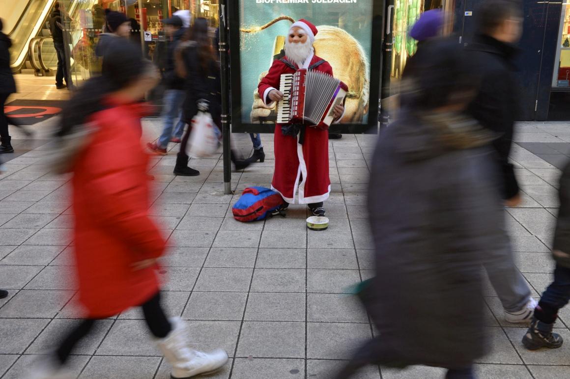 Suécia, Estocolmo. Um músico-Pai Natal toca em troca de umas moedas