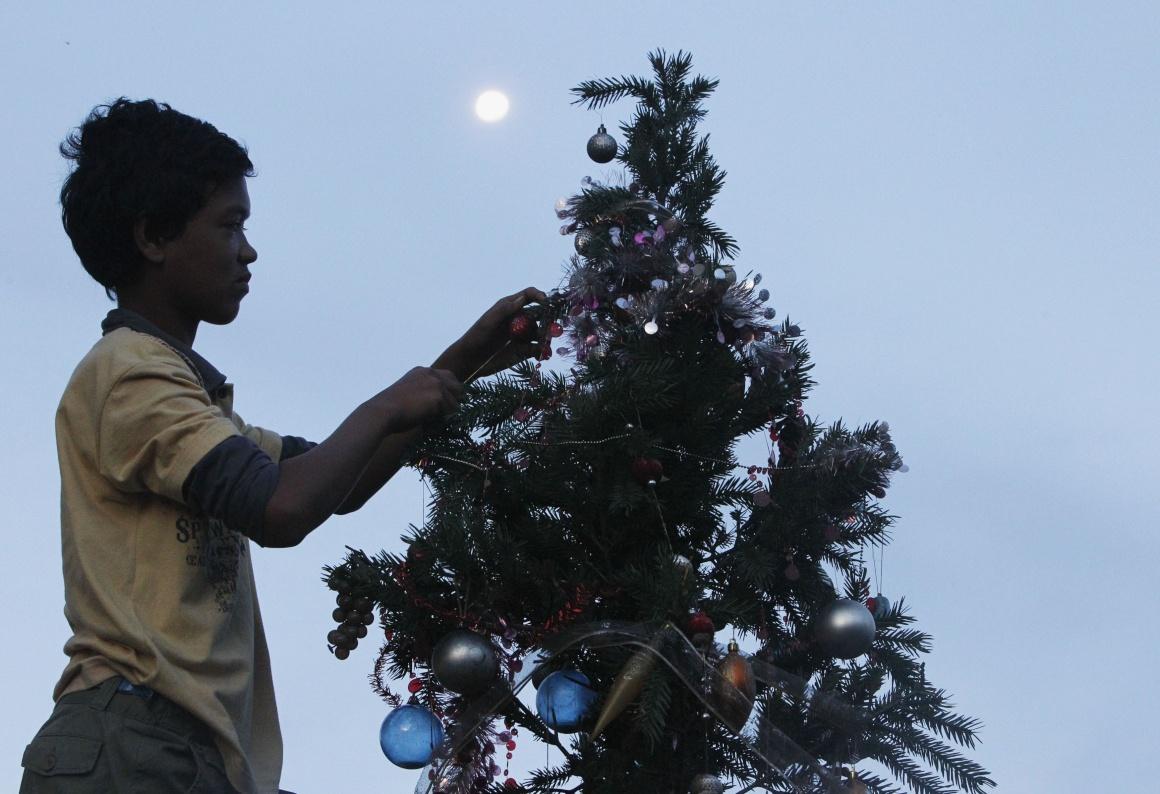 Ruben Miraflor, de 15 anos, sobrevivente do supertufão Haiyan, decora uma árvore de Natal em Magalhães (Magallanes, assim baptizada em homenagem a Fernão de Magalhães)