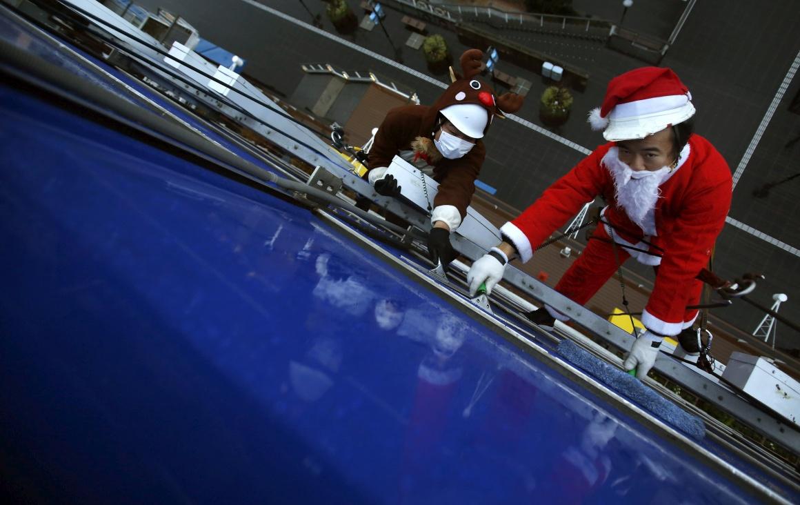 Japão, Tóquio. Lavadores de janelas com fatiota de Pai Natal nas alturas
