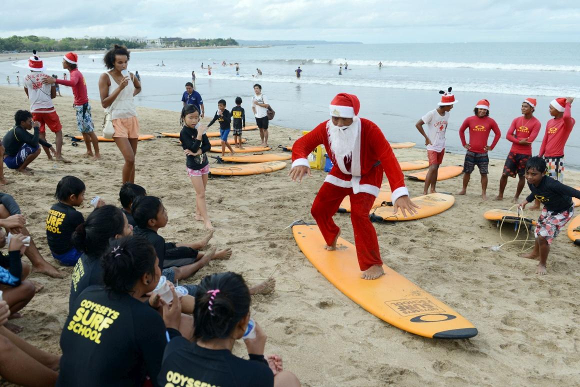Indonésia, na ilha de Bali, praia de Kuta. Vestido de Pai Natal, o sufista dá aulas a crianças de um orfanato antes de os levar a surfar