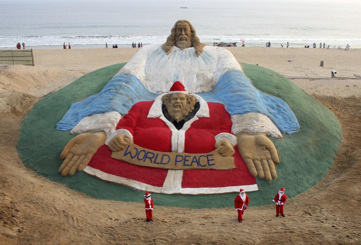 Índia, Puri (Odisha). Uma criação do artista indiano Sudarshan Pattnaik, em areia, juntou Jesus e o Pai Natal em nome da