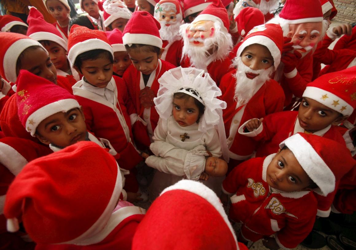 Índia. Rapazes vestidos de Pai Natal, uma menina como a Virgem Maria segurando um