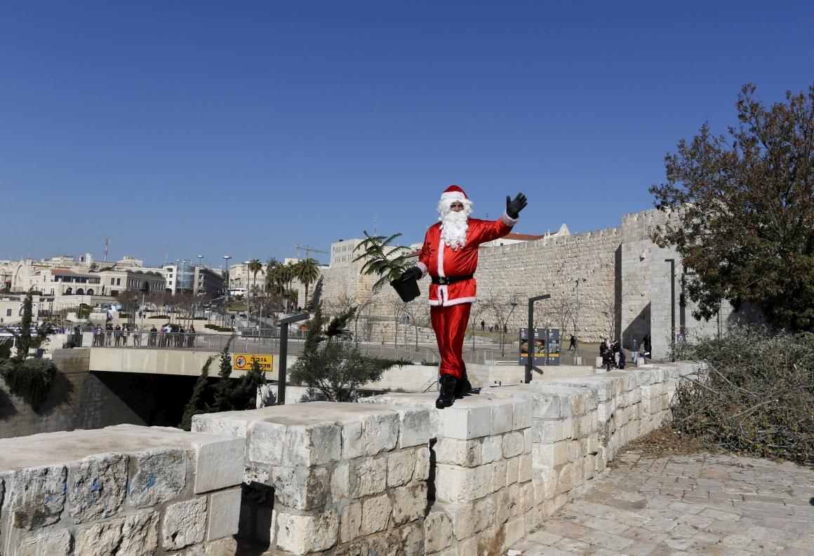 O israelo-árabe Issa Kassissieh, vestido de Pai Natal, segura uma pequena árvore de Natal no centro histórico de Jerusalém