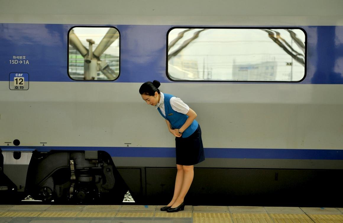 COREIA DO SUL, 28.08.2013. Uma assistente de bordo do comboio saúda os passageiros que chegam à estação de Seul