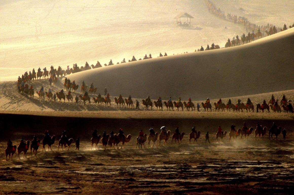 CHINA, 4.10.2013. Turistas em passeio de camelo durante a