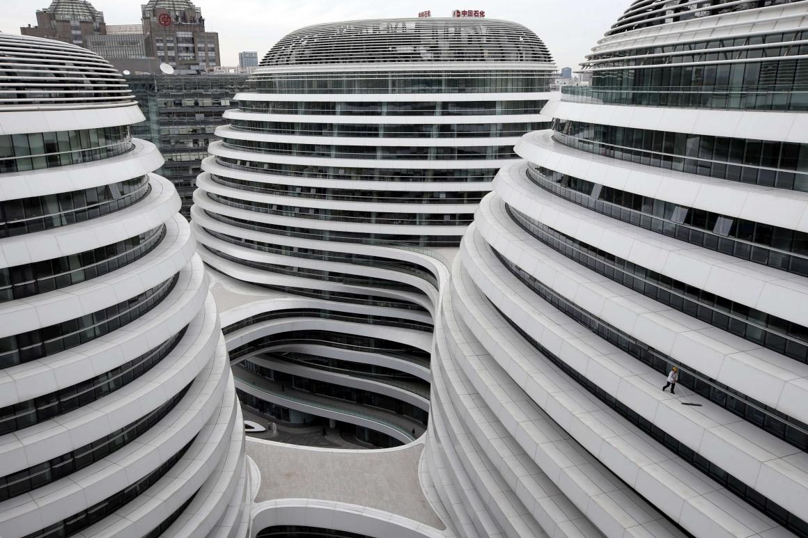 CHINA, 14.10.2013. A nova geometria chinesa. Um trabalhador limpa o chão de um nível deste novo complexo de escritórios e lojas em Pequim.