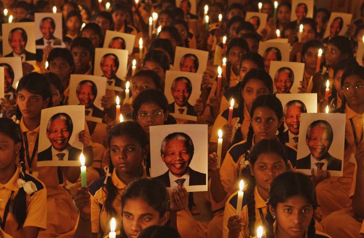 ÍNDIA, 6.12.2013. As homenagens a Nelson Mandela após a sua morte foram planetárias. Aqui, um exemplo local na Índia: crianças da escola primária seguram retratos de Mandela durante uma cerimónia em Chennai