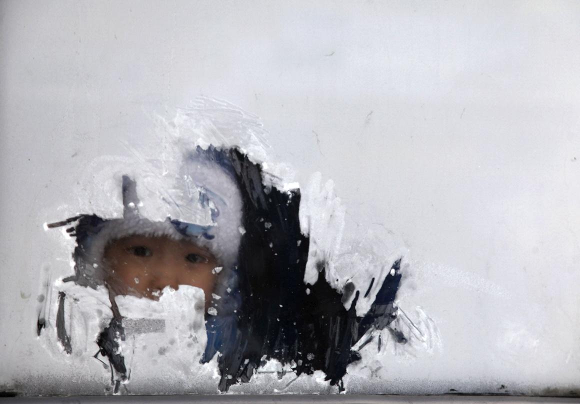 MONGÓLIA, 27.12.2013. Uma criança espreita pela janela de um autocarro em Ulan Bator. Temperatura: -31ºC
