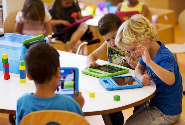Algumas crianças usam o iPad para brincar