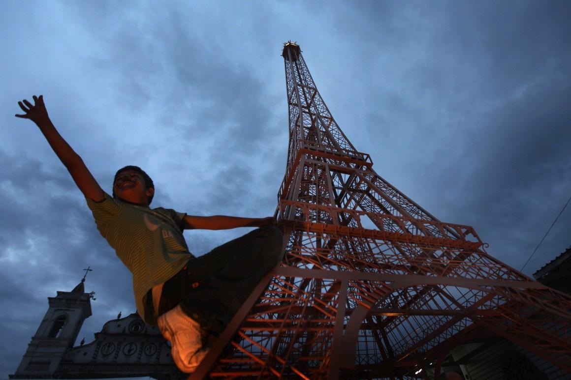 Um rapaz brinca numa réplica da torre na praça de Los Dolores em Tegucigalpa, Honduras. Uma oferta da embaixada francesa nas Honduras, em 2010, celebrando os 221 anos de independência do país. Foi a primeira réplica no América Latina e a 18ª no mundo.