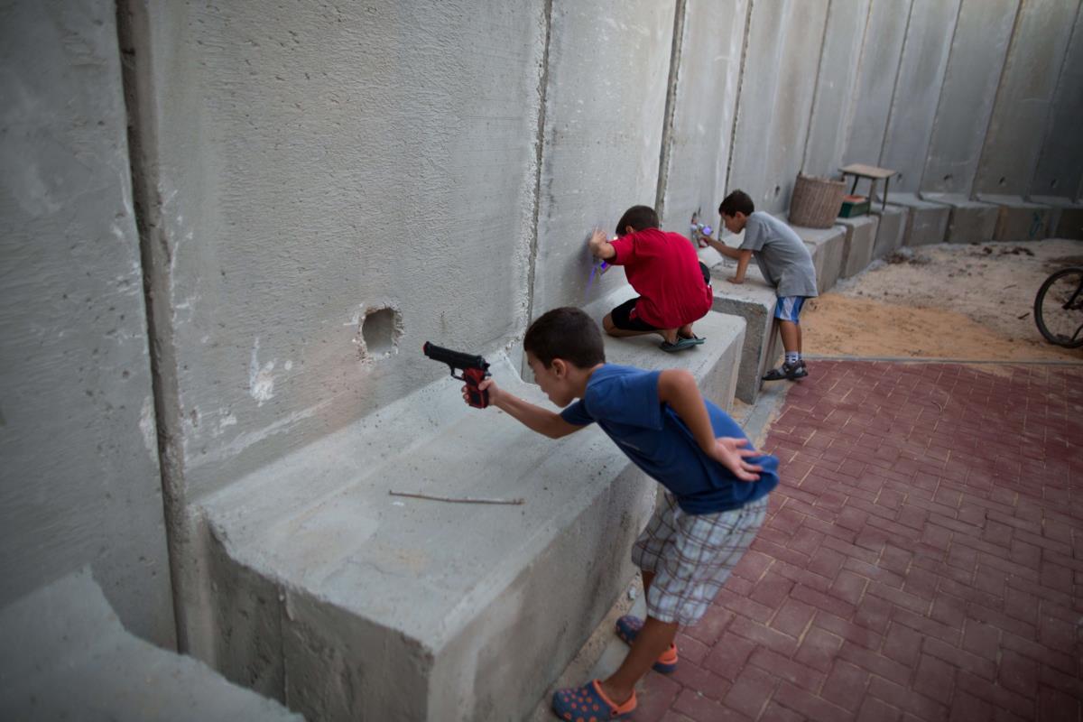 Crianças israelitas com pistolas de brinquedo, junto do muro de protecção da sua escola no Kibbutz Nahal Oz