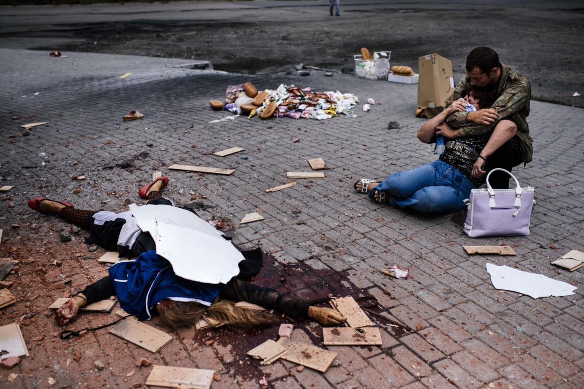 Mãe e irmão choram a morte da sua filha e irmã, em Makiyivka, Ucrânia