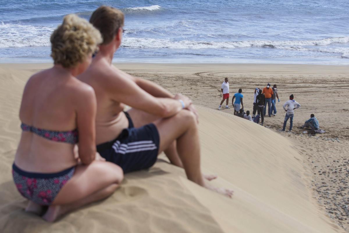 Turistas olham para imigrantes africanos que deram à costa na praia de Maspalomas, Canárias