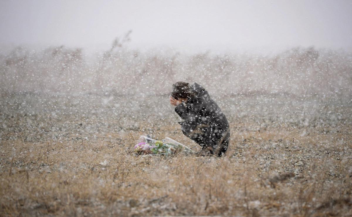 Uma mulher chora pelas vítimas do terramoto e tsunami, Iwate, Japão
