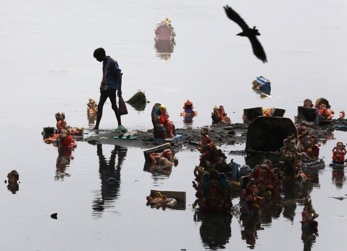 Um rapaz apanha objectos oferecidos ao deus Ganesh, Ahmedabad, Índia