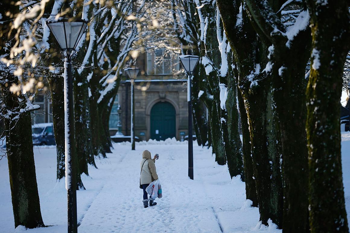 Em Buxton, no centro de Inglaterra, uma mulher caminha entre o nevão