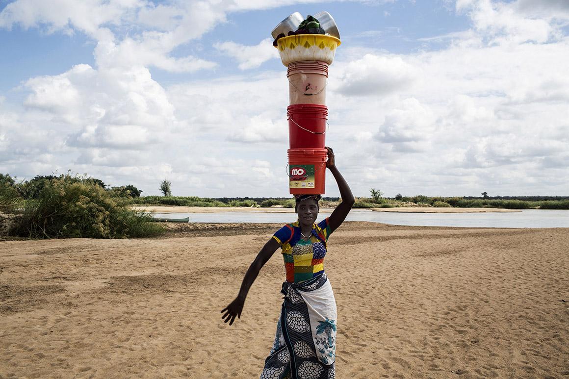 Mulher transporta na cabeça utensílios domésticos nas margens do rio Rovuma, Moçambique