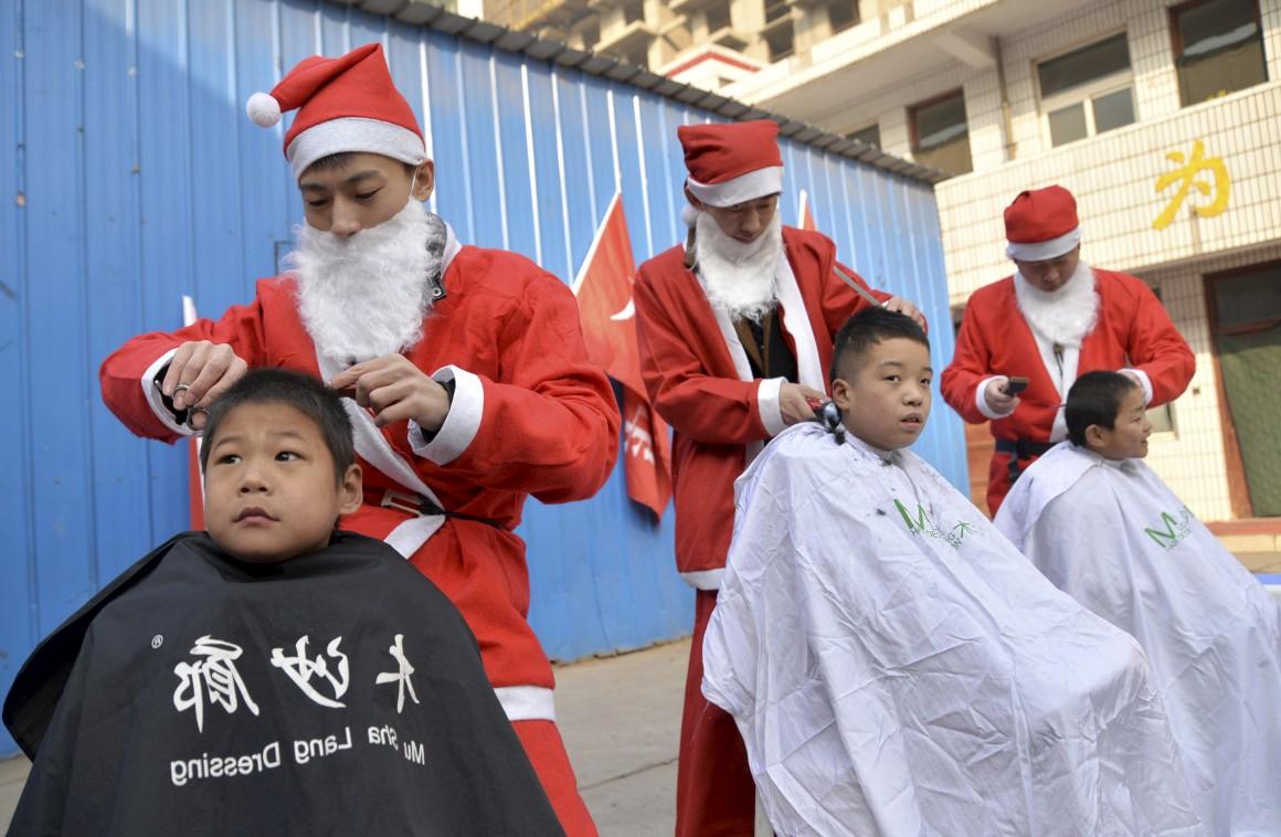 China, Handan. Voluntários vestidos de Pai Natal cortam o cabelo de rapazes de um centro de apoio