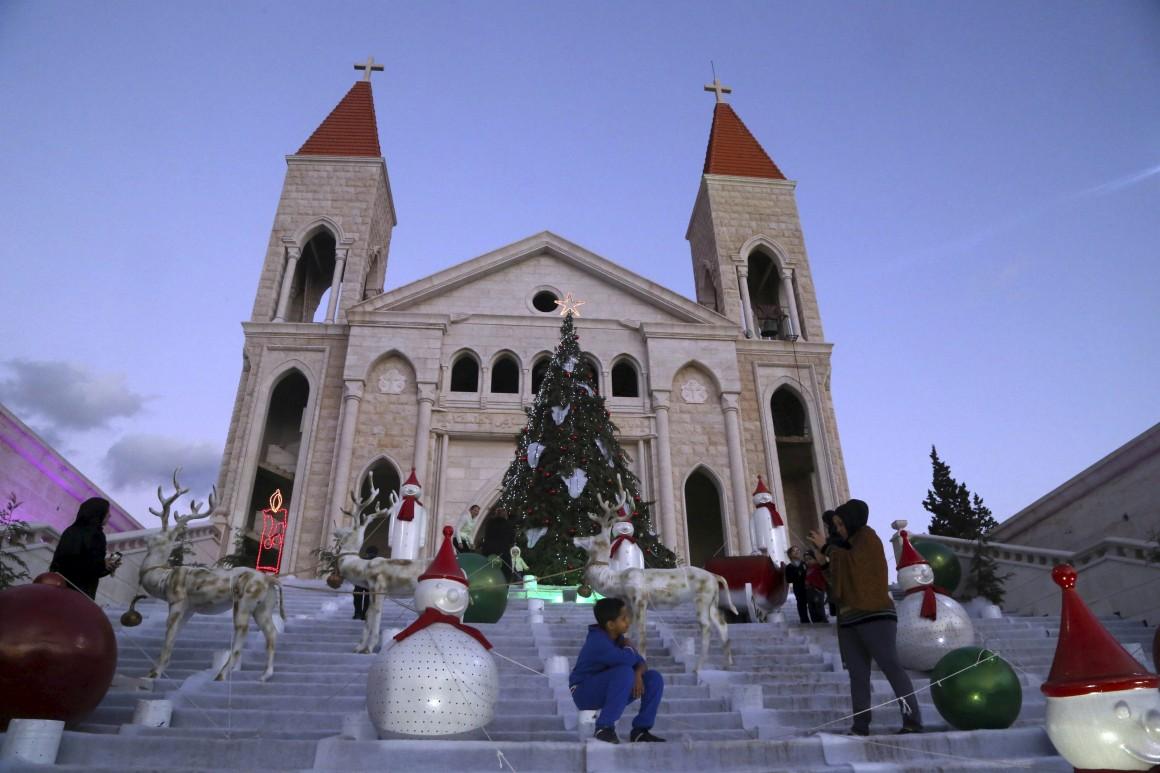 Líbano, crianças posam para a foto frente a uma igreja de Jiyeh