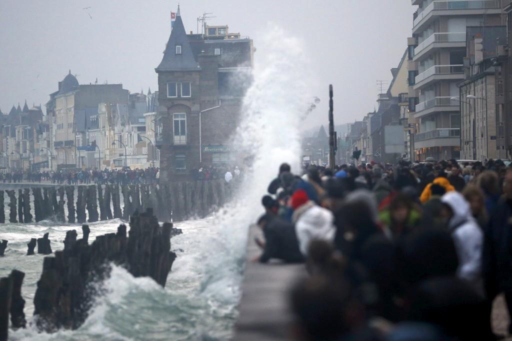 Enchente de curiosos na frente costeira de Saint Malo, à espera do pico da maré alta