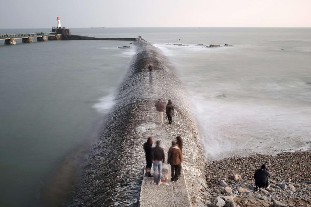 Curiosos passeiam no paredão do porto de Les Sables-d'Olonne, Oeste de França