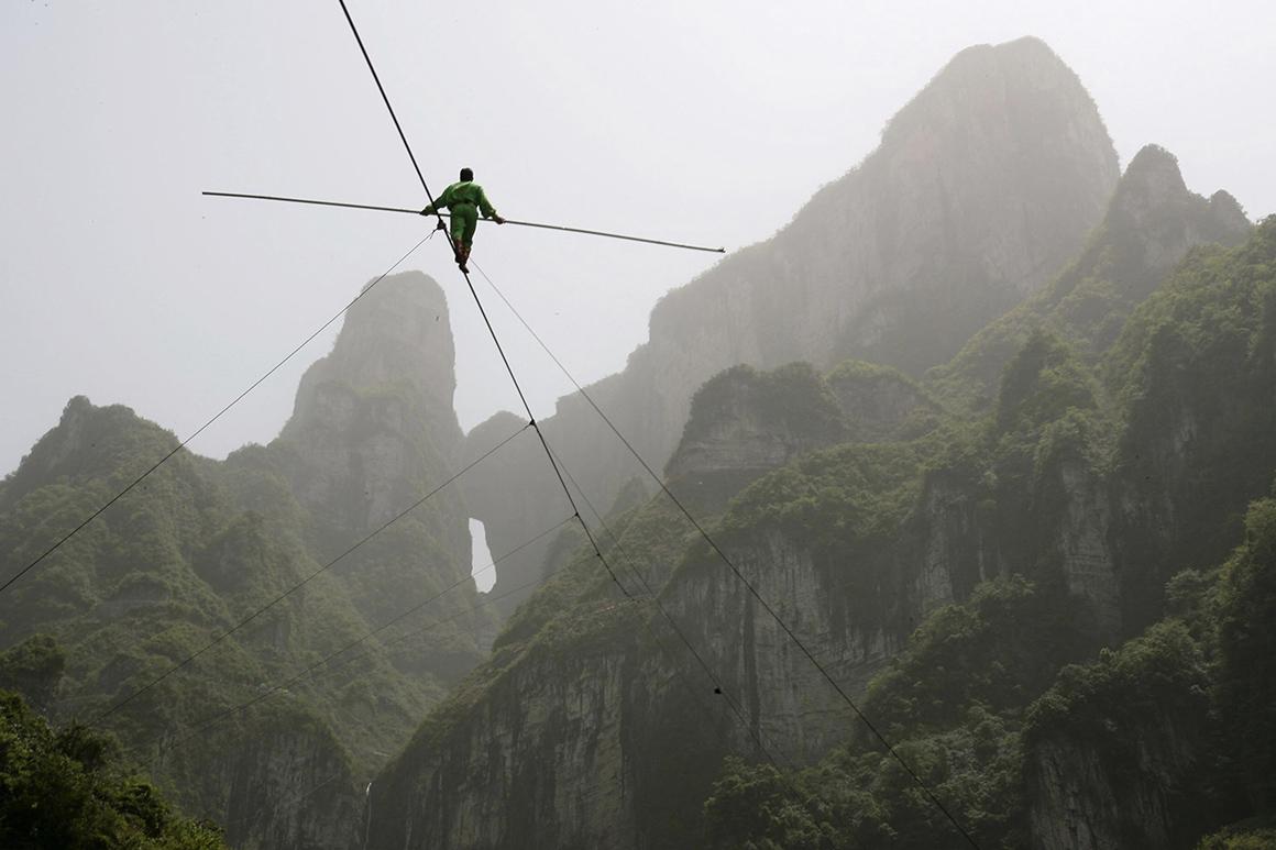 O chinês Samat Hasan caminha numa corda bamba sobre Zhangjiajie, na província de Hunan, batendo o recorde mundial: 700 metros de cabo, com 3,1 centímetros de diâmetro e uma inclinação de 39º.