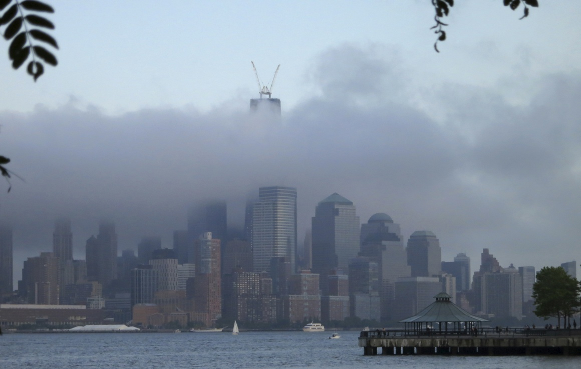 Nova Iorque, ao longo do rio Hudson enquanto as nuvens envolvem o One World Trade Center.