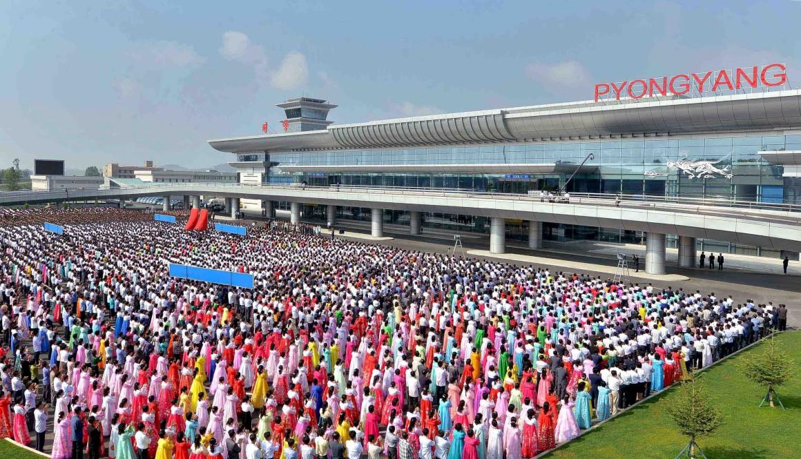 Cidadãos norte-coreanos aguardam pela cerimónia de inauguração do terminal
