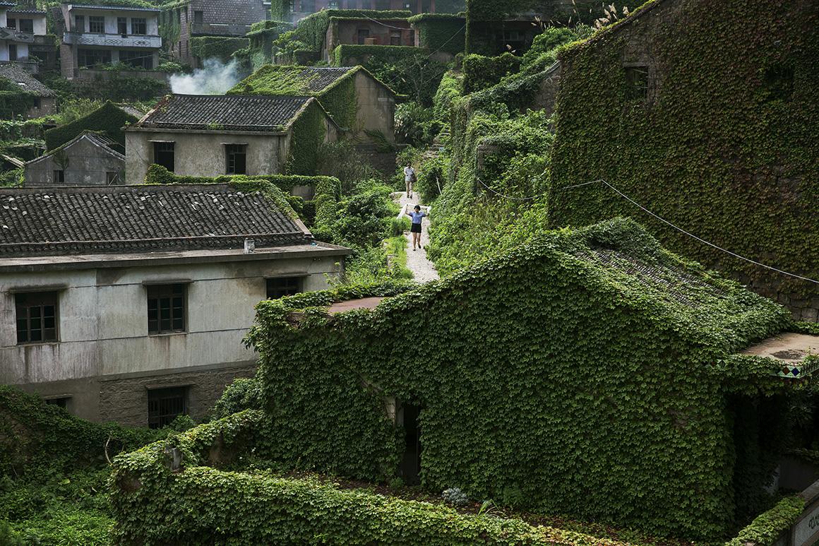 Turistas passeiam entre os edifícios cobertos de vegetação da antiga vila piscatória