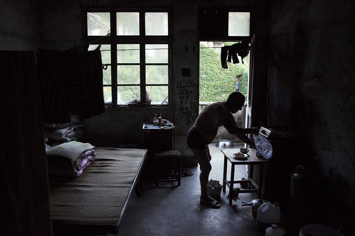 Sun Ayue prepara o jantar na casa onde vive em Houtouwan