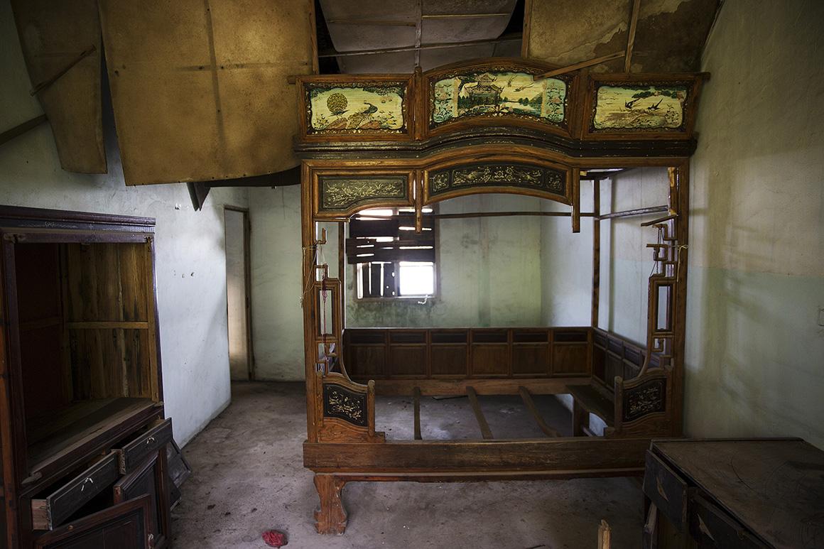 Uma cama e outros móveis foram deixados num quarto de um pequeno apartamento na vila abandonada