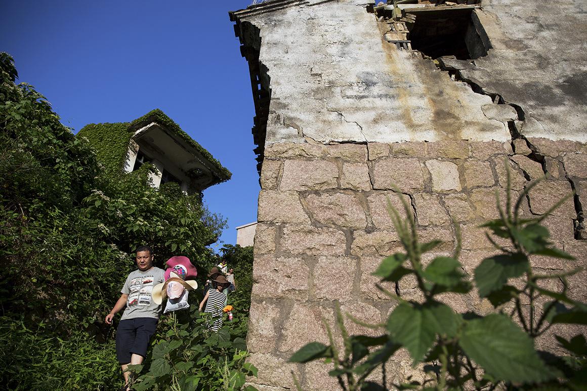 Todos os dias, centenas de turistas visitam Houtouwan, passeando pelos trilhos estreitos entre o casario coberto de vegetação