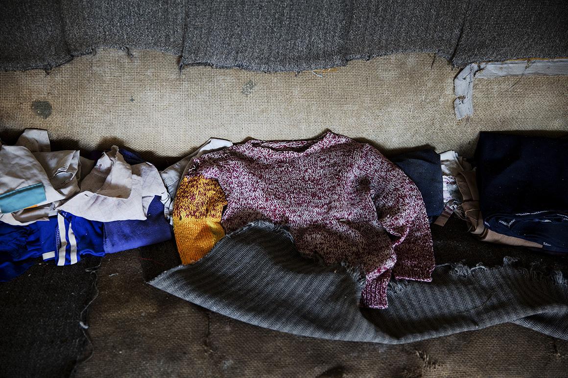 Roupas de criança foram deixadas sobre um sofá de uma casa abandonada