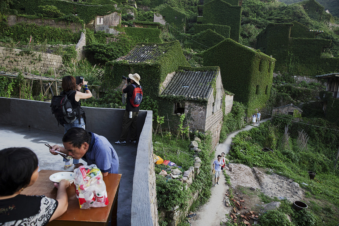 Xu Yueding e Tang Yaxue deixaram de morar em Houtouwan há mais de 20 anos, mas agora regressam todos os dias à antiga casa, onde acolhem turistas e lhes vendem garrafas de água, o único item disponível para compra na vila