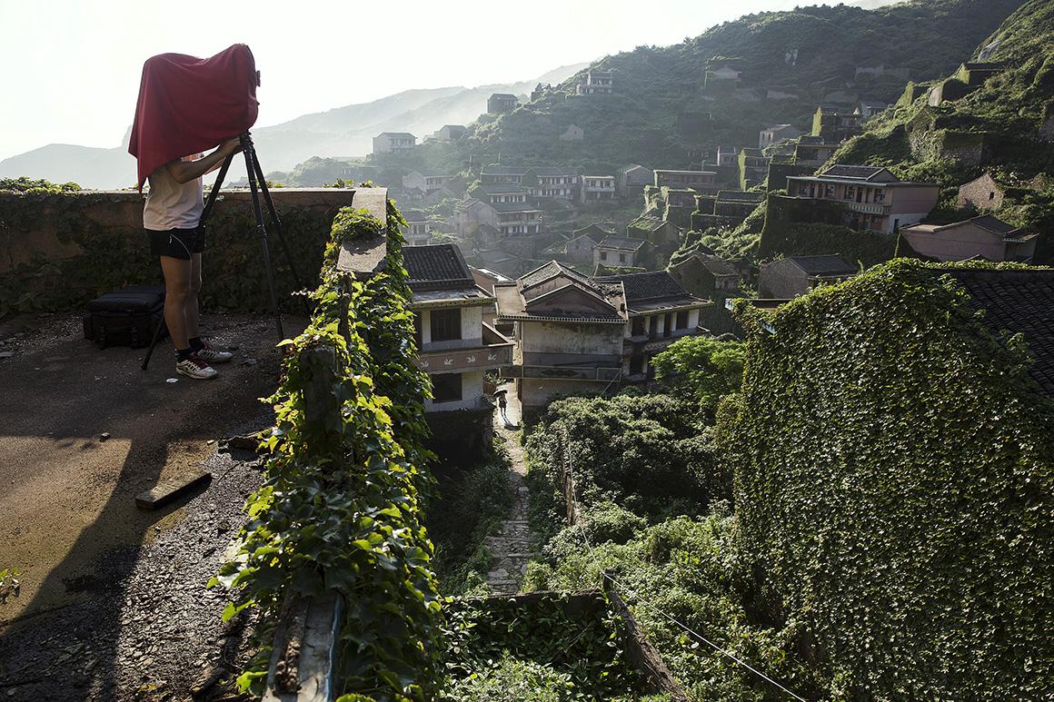Um fotógrafo regista a visita de turistas a Houtouwan