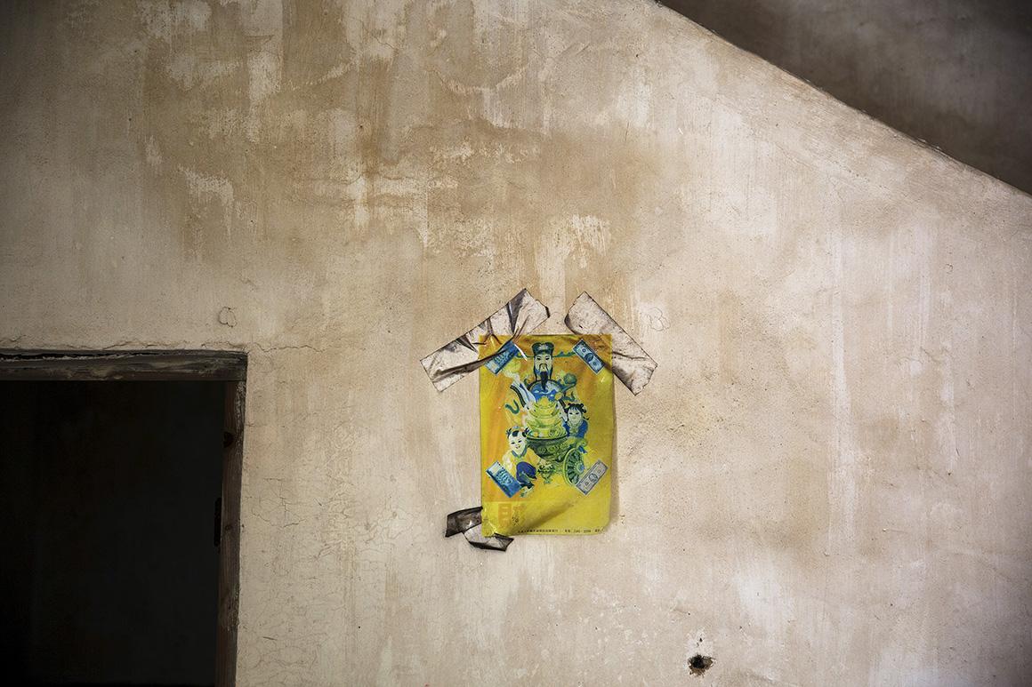 Um quadro do deus chinês da fortuna permanece pendurado numa casa abandonada da vila