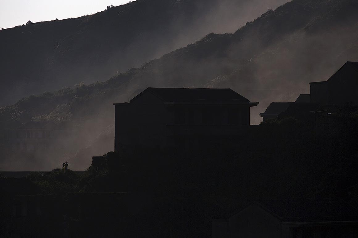 Uma mulher tira uma fotografia à vila enquanto o nevoeiro matinal ainda cobre o casario