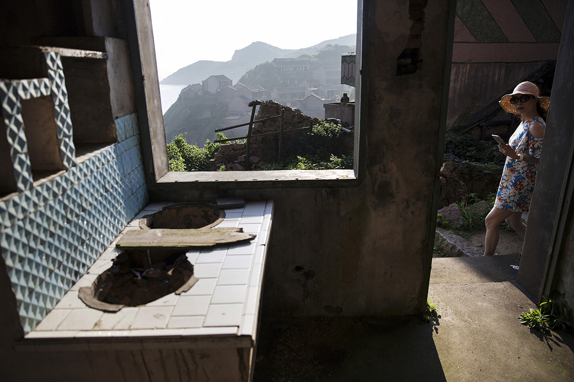 Uma turistas espreita para uma casa abandonada em Houtouwan