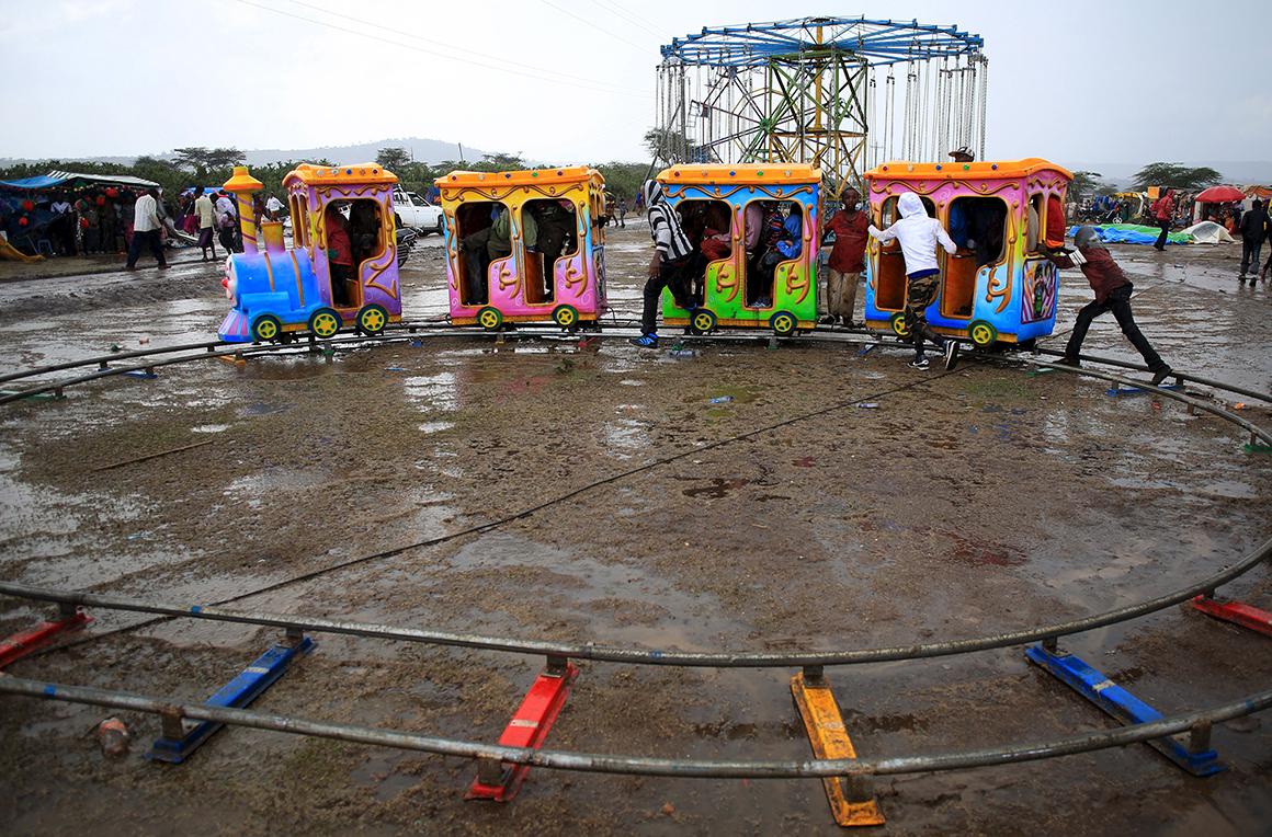 Crianças brincam num comboio infantil durante a chuva