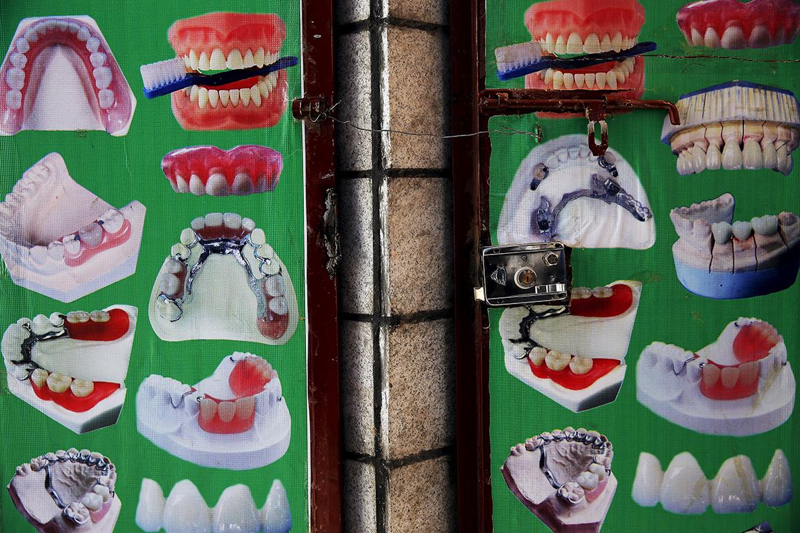 Fotografias colocadas à porta de um dentista na zona antiga da cidade