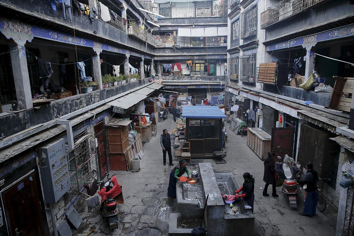 Mulheres lavam a roupa num pátio na zona velha da cidade