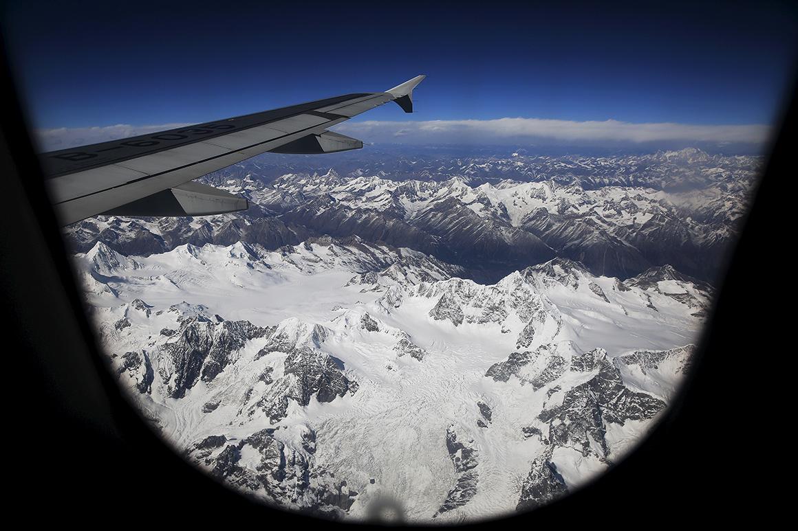 As montanhas tibetanas surgem cobertas de neve à medida que o avião sai de Lhasa