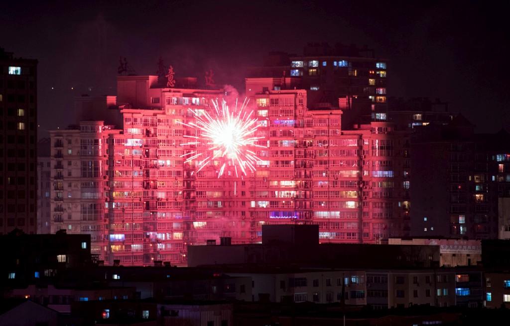 Fogo de artifício iluminando edifícios da cidade fronteiriça chinesa de Dandong, em frente à cidade norte-coreana de Sinuiju