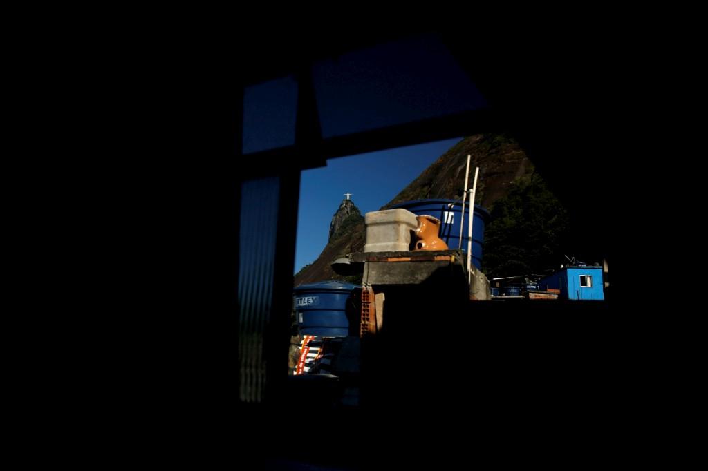 A estátua do Cristo Redentor é vista através de uma janela do albergue Cena na favela Santa Marta