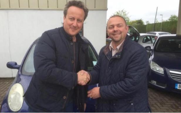 O primeiro-ministro com o dono do stand de automóveis da terra