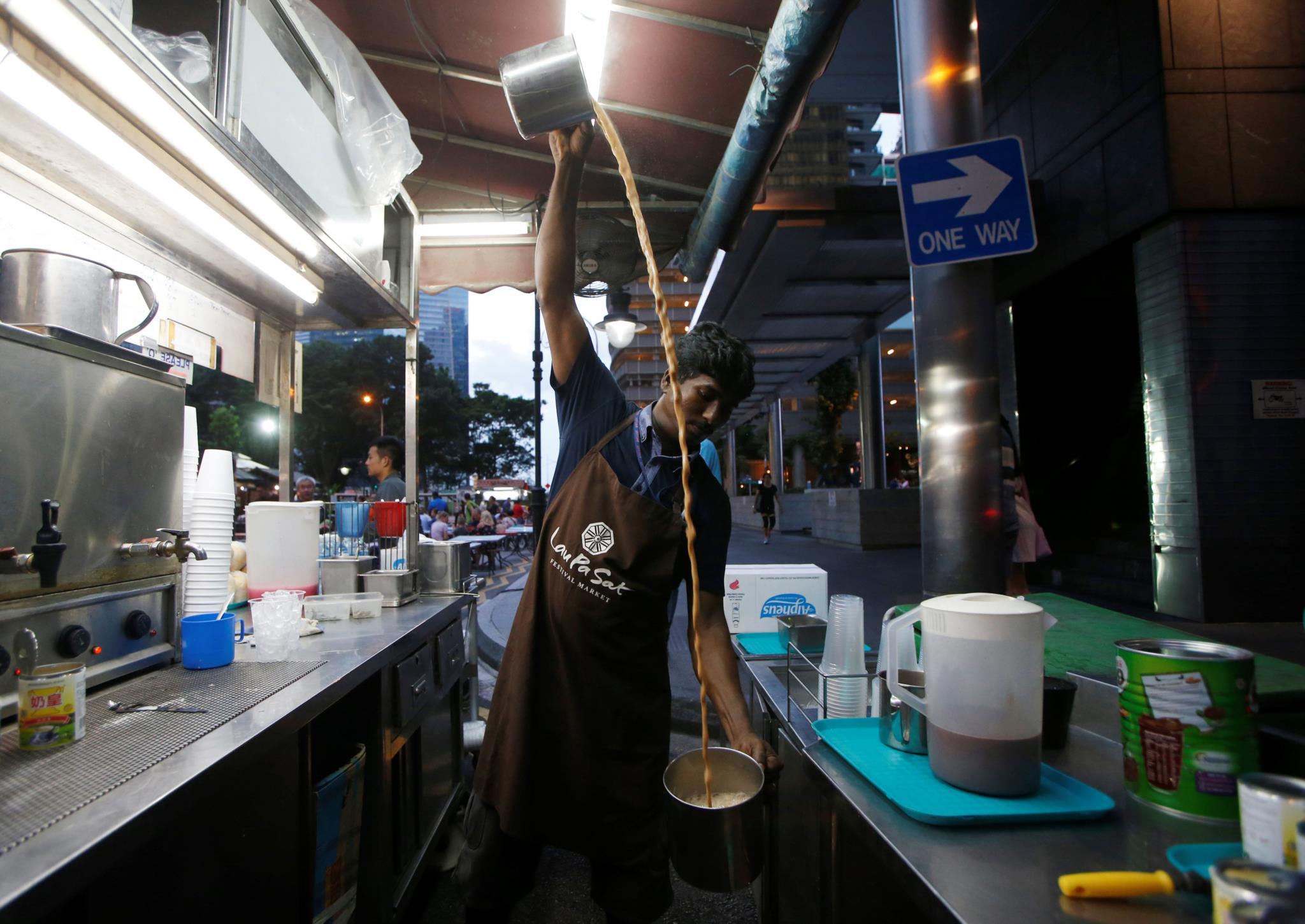 Um vendedor ambulante prepara <i>Teh tarik</i>, um chá típico de Singapura. Para esfriar o chá e misturá-lo com o leite condensado, a bebida é