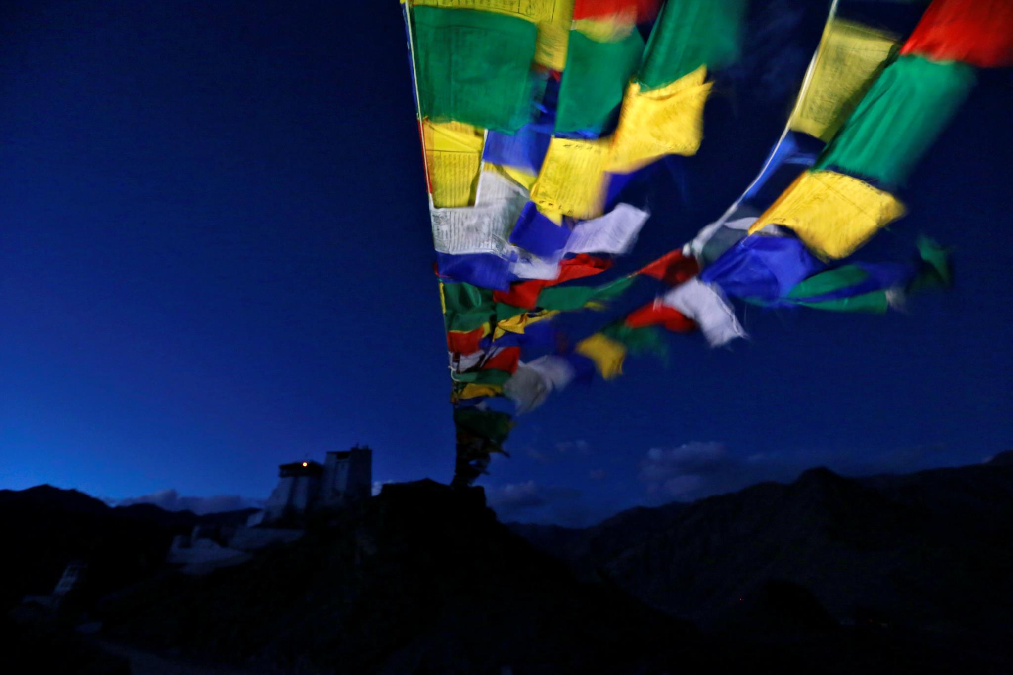 Bandeiras de oração tibetanas esvoaçam junto ao mosteiro de Tsemo, em Leh