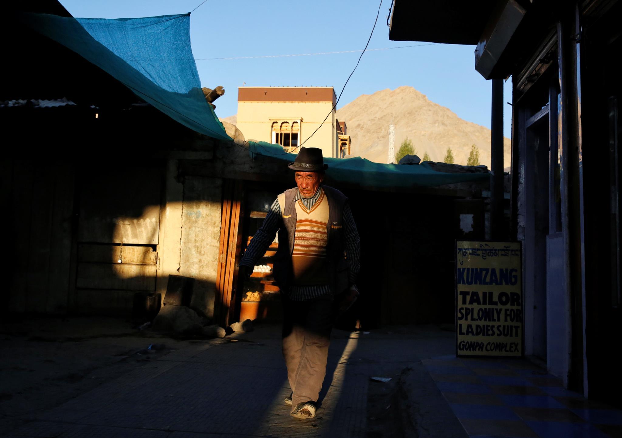 Um velho passa por entre uma rua de lojas em Leh