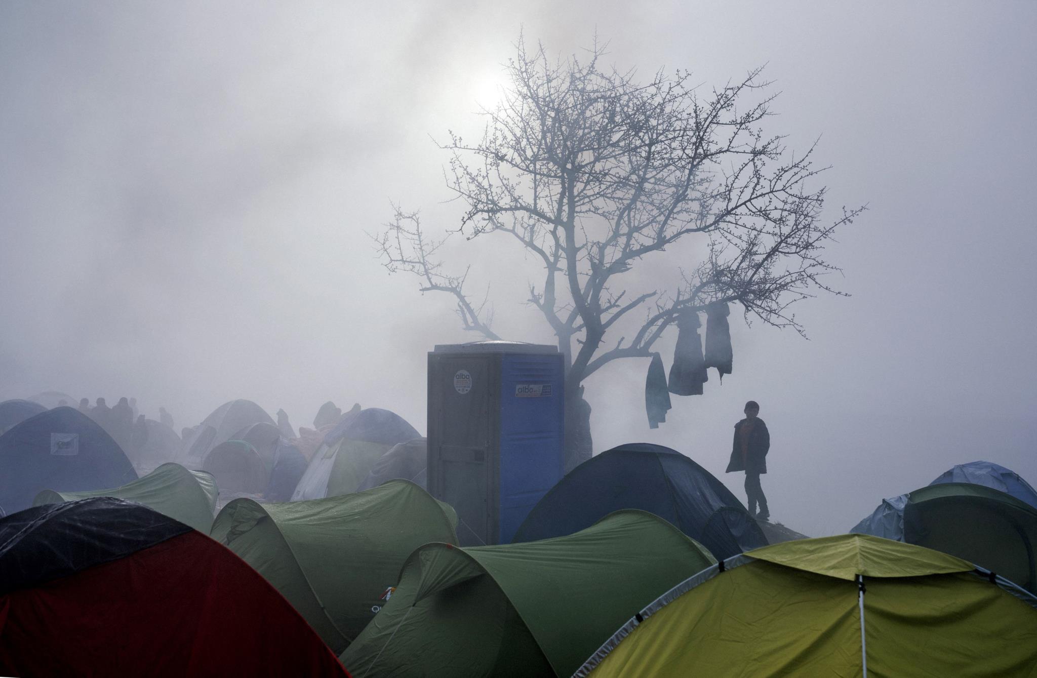 Refugiados esperam para atravessar a fronteira entre a Grécia e a Macedónia