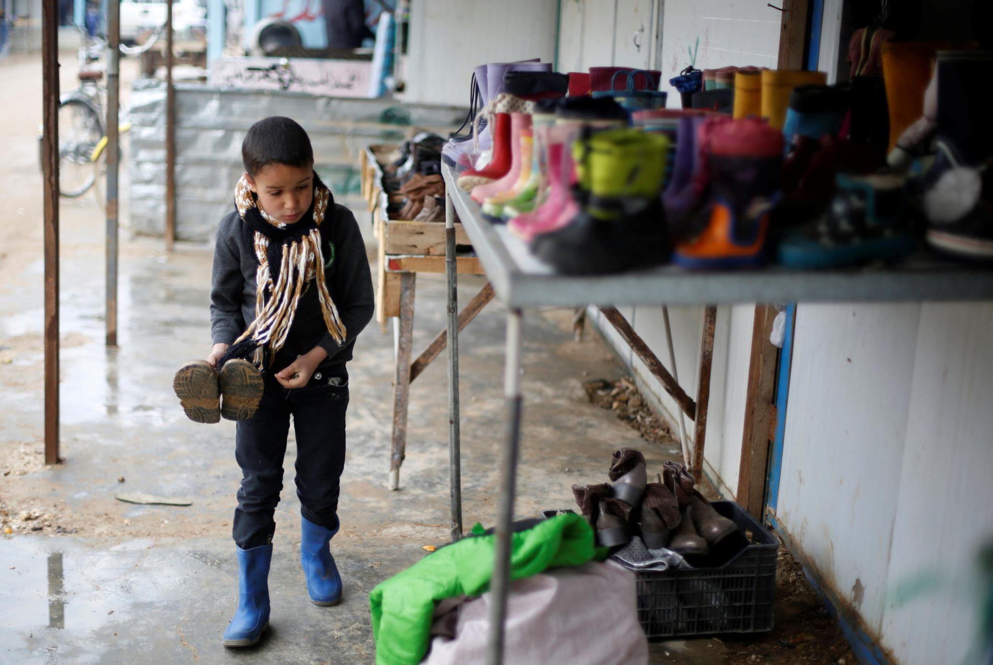 Uma criança síria procura umas botas de Inverno num campo de refugiados em Mafraq, Jordânia